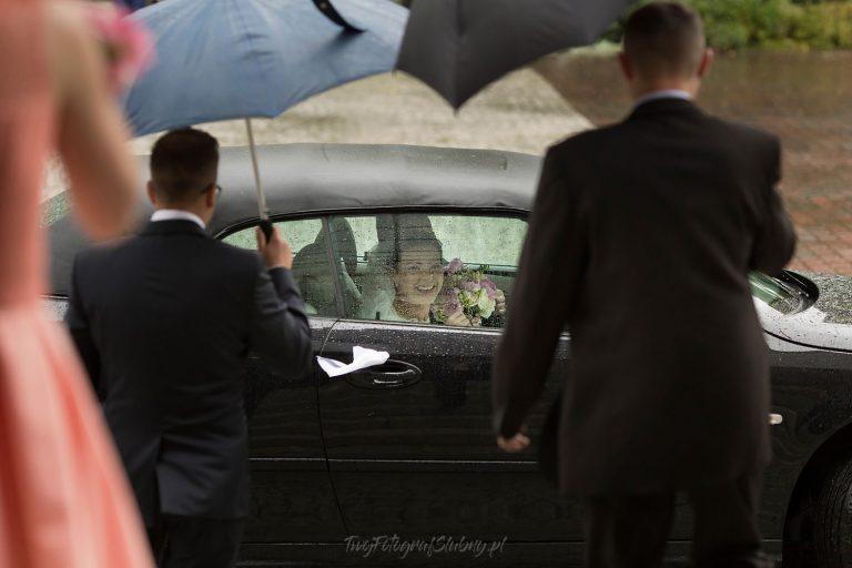 usmiechnieta pani mloda szykuje sie do wysiadania z auta w czasie deszczu KiM 0332